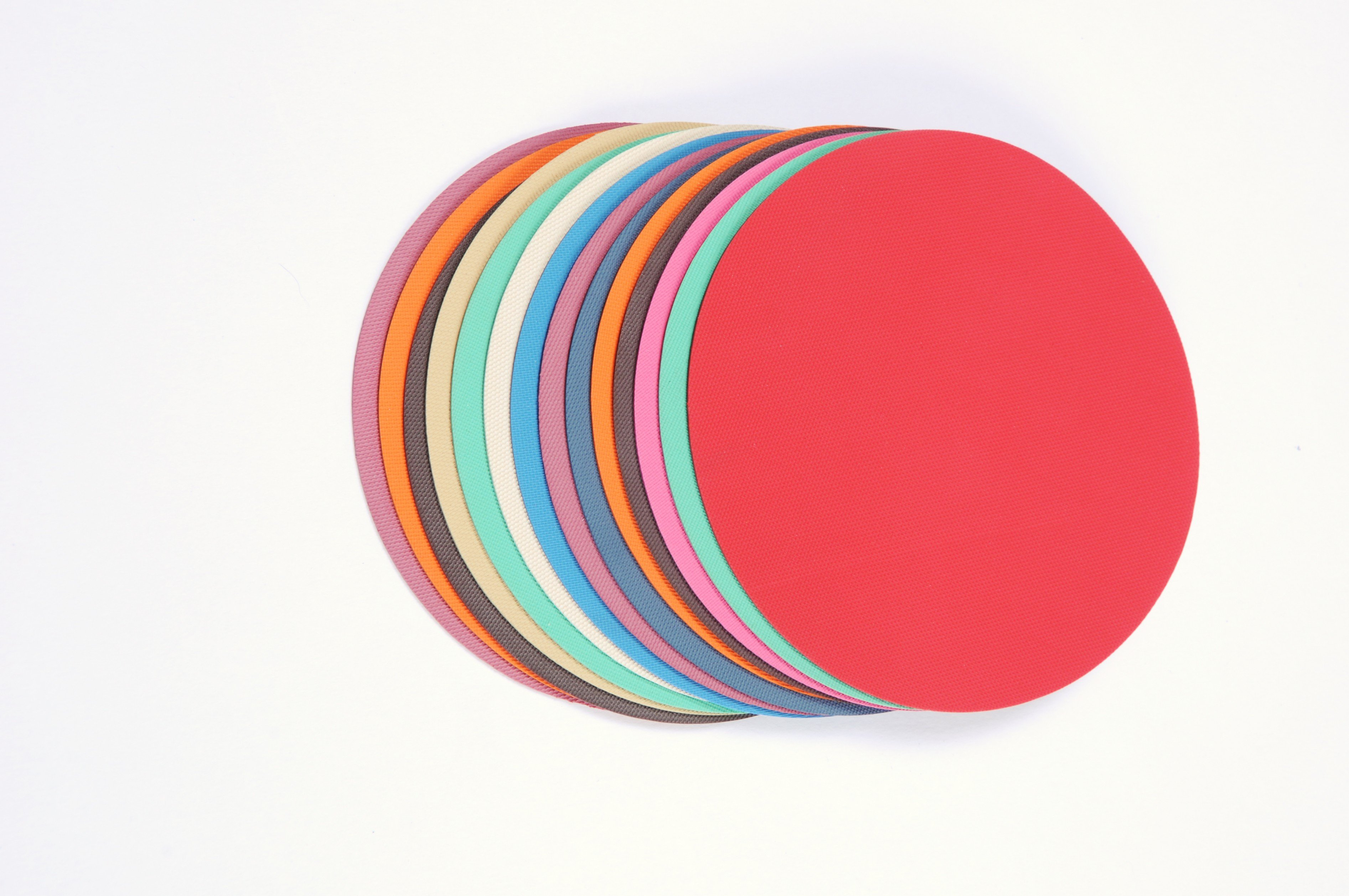 Stacked Colored Sheet Rubber Cut Circles with Different Fabric Finishes